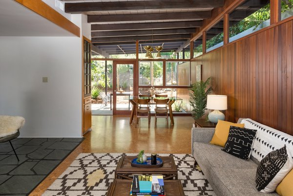 The living room is capped by a dining area at the other end, where another wall of glass opens to the other side of the home, creating the potential for lovely cross breezes.