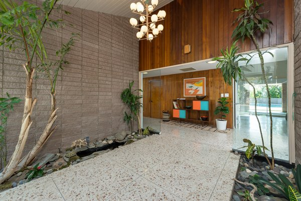 The stunning interiors feature an authentic midcentury-modern material palette that includes original terrazzo flooring, brick, and warm wood paneling.