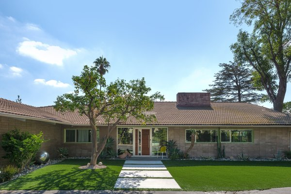 The well-preserved midcentury home sits on a half-acre lot near the Knollwood Country Club in Granada Hills. The lot features a gorgeous outdoor space that includes a sprawling lawn, a covered patio, and a swimming pool and spa.