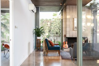 Extensive glazing and a strong wood-burning fireplace define the living room.