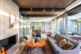 This angle shows the open-plan layout, as well as the living space that blends into the dining area. The exposed wood tongue-in-groove ceilings have been preserved, while additional lighting has been added.