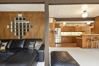 Classic midcentury features such as wood paneling, globe pendant lighting, and beams appear throughout the home.