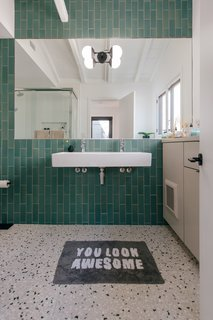 The new bathroom features Terrazzo flooring from Concrete Collaborative and gorgeous green tiles from Heath Ceramics.