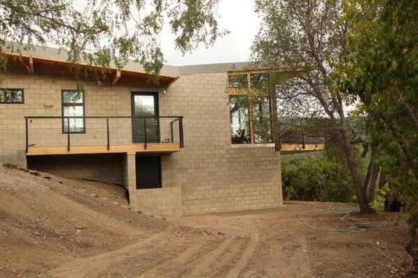 The 1100-square-foot home is located on a hill surrounded by oak trees.