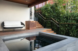 A lower-level patio with benches and a generously sized spa allows the homeowner to enjoy the view while entertaining company. The stairs are made from naturally fire-resistant ipe wood.