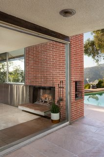 The corner fireplace has a barbecue feature on the exterior, overlooking the pool.