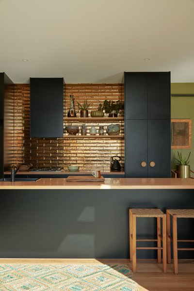 The kitchen backsplash tiles are Perini tiles in jaca bronze, their metallic glaze reflecting the natural light.