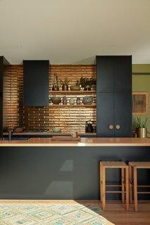 The kitchen backsplash tiles are Perini tiles in jaca bronze, their metallicglaze reflecting the natural light.