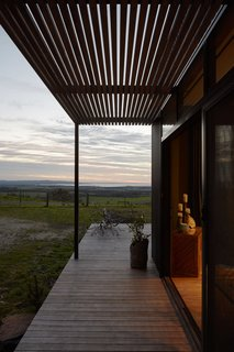 The prefab's external cladding is corrugated Colorbond in woodland gray; the pergola features natural timber hardwood battens.