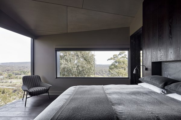 The bedroom also boasts a wall of sliding glass doors that open the home to its surroundings.