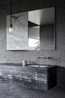 The bathroom wall tiles are a Japanese product from Inax, called Sekhia. The sink vanity is made from Black Marquina marble, and the aged bronze faucets were sourced from Brodware.