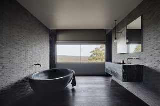 The dramatic, handmade, black concrete soaking tub is from Boyd Alternatives, a local Victorian company that produces handmade baths. The color is an addition to the concrete mix.