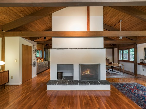The central hearth includes space for firewood storage. The kitchen is off to the left, and the dining room is to the right.