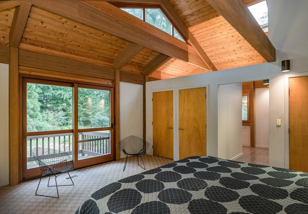 Clerestory windows and skylights flood the bedroom with natural light, and mahogany-framed sliding doors lead to the balcony.