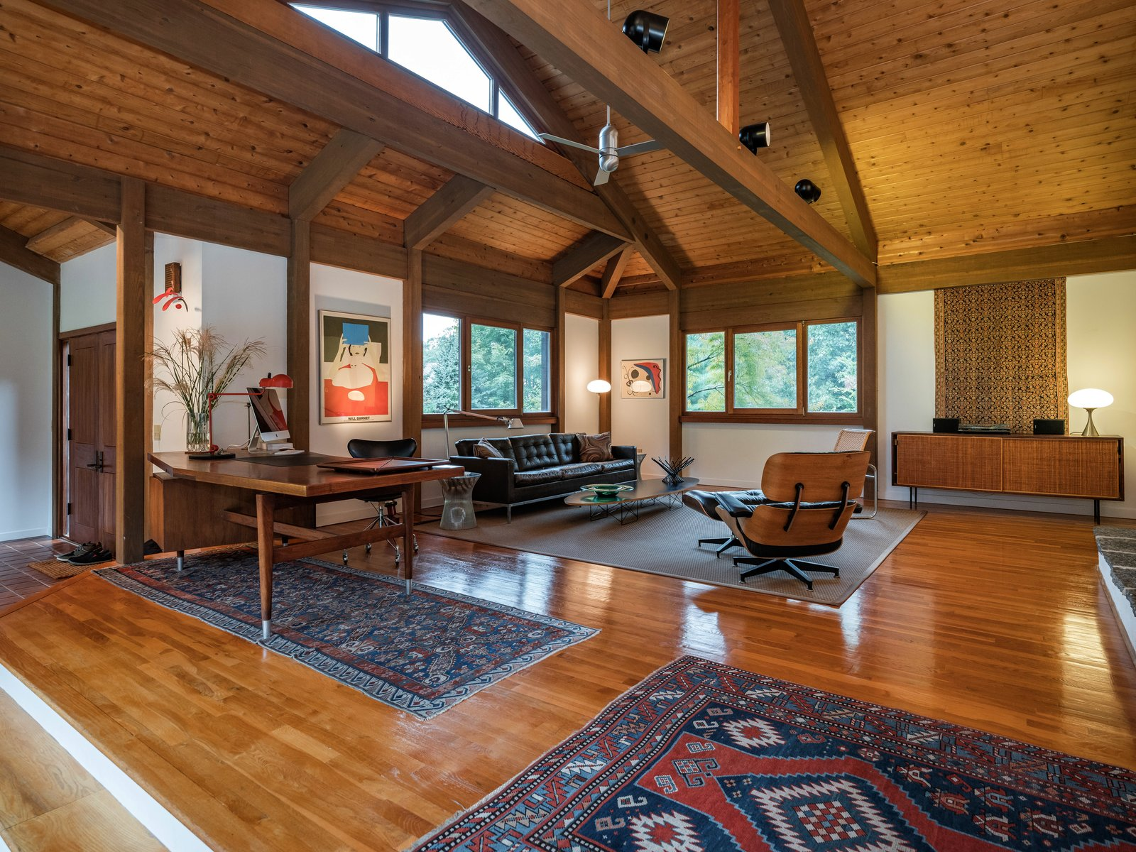 Living Room, Medium Hardwood Floor, Ceiling Lighting, Chair, Sofa, Storage, Console Tables, Lamps, Coffee Tables, and Table Lighting  Photo 1 of 16 in A Midcentury-Inspired Post-and-Beam Home Hits the Market in Connecticut For $595K