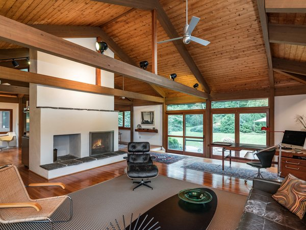 The central fireplace anchors the open-plan living space and serves as a divider between the rooms. Mahogany-framed sliding doors lead out to the deck. The living space features oak floors throughout.
