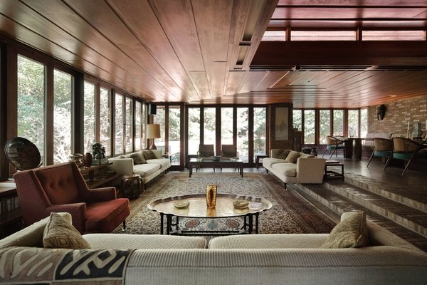 A slightly more formal great room is lined with floor-to-ceiling windows.  Note how the sofa is built into the steps.