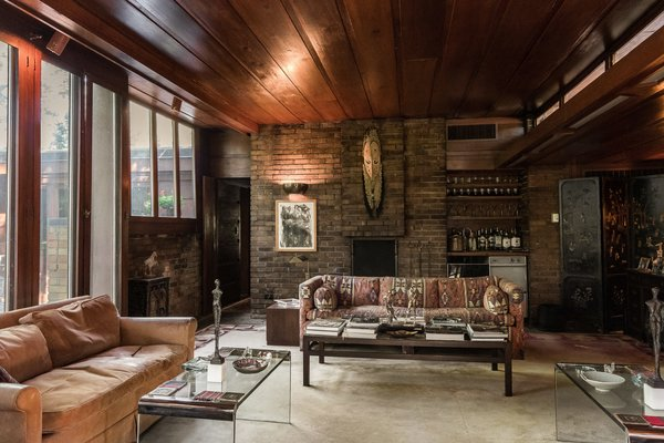 Large windows, a rich wood paneled ceiling, and brick make up this cozy living room.