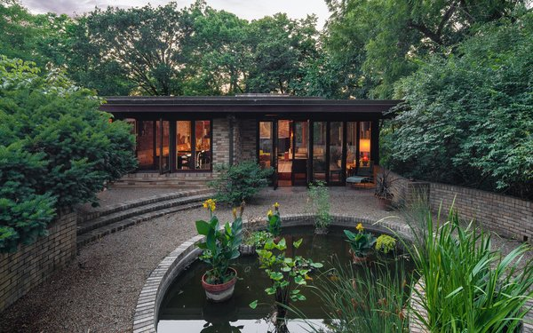 The home is elegantly set into its surroundings and overlooks a serene garden patio with a koi pond.