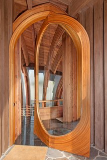 The front door opens to the Lotus House's central light-filled three-story glass atrium.