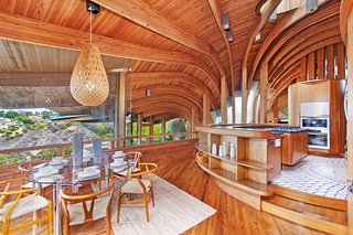 The curvilinear individually-treated Douglas Fir beams cascade out from the central atrium. This is a look at the kitchen which features built-in teak cabinetry and an original light fixture over the table.