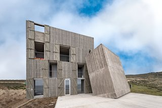 Two of the weathered concrete volumes lean against each other like building blocks. The main volume is spread over four levels.