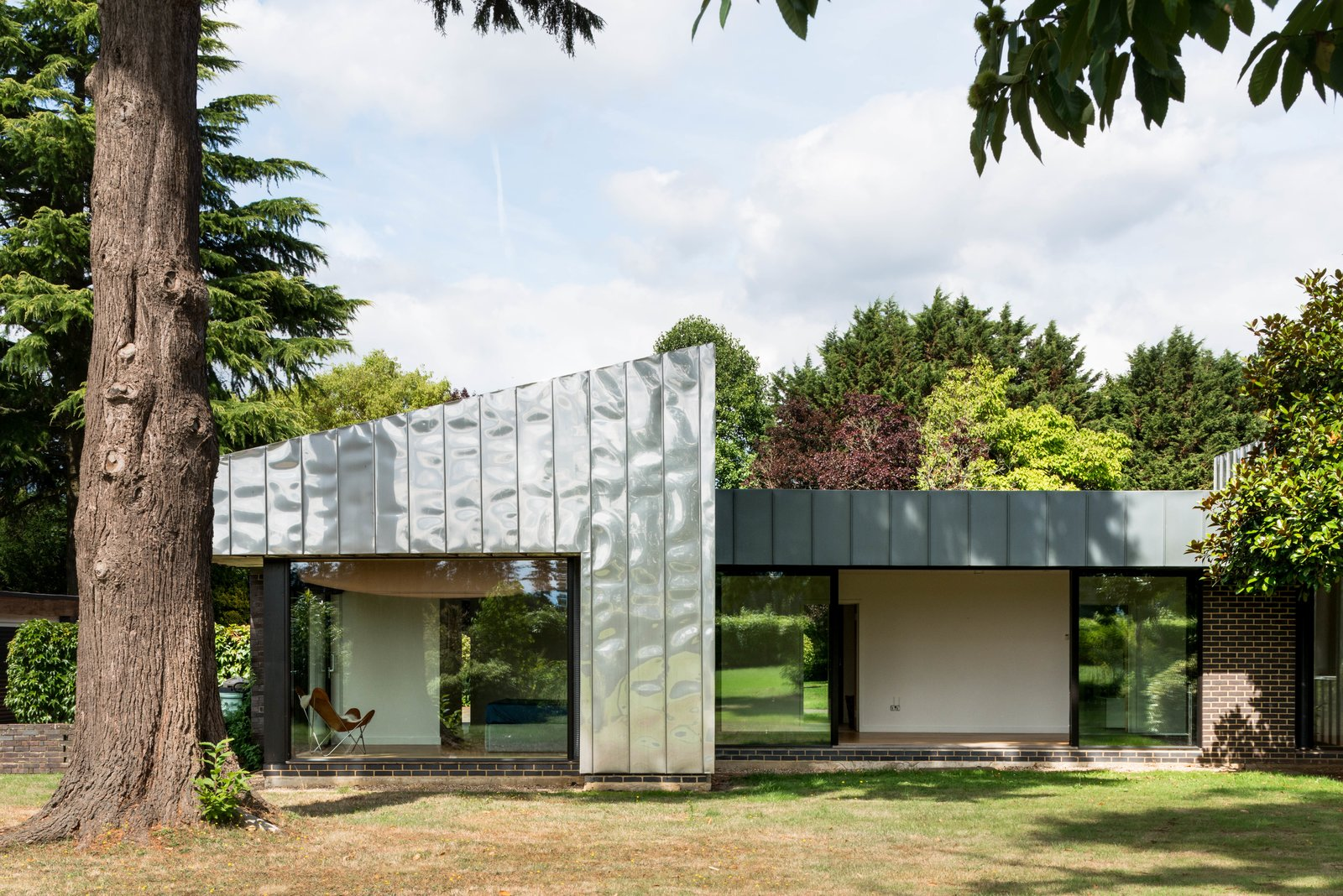 Exterior, Flat RoofLine, Metal Siding Material, Metal Roof Material, Brick Siding Material, Glass Siding Material, Mid-Century Building Type, and House Building Type  Best Photos from Clad in Stainless Steel, a Commanding Midcentury in England Wants $3.2M