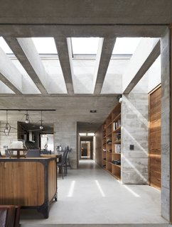 Rectangular skylights help bring natural light into the home, offsetting the heaviness of the concrete volume.