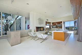 Full-height windows provide the living room with lots of natural lighting. A generous fireplace anchors the room.