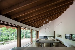 The ceiling features exposed woodbeams which extend straight out to the eaves.