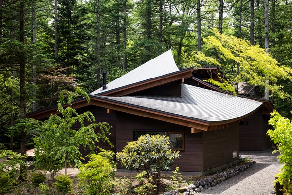 The roofs' concave and convex forms are elegantly layered and integrated into the home's forested setting.