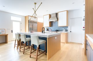 The new kitchen features appliances from Subzero and Wolf, and custom built-in cabinets that match the ones in the den. The brass light fixture over the island is from Maker & Moss.