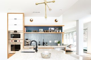 """Myers used terrazzo slabs from Concrete Collaborative to fabricate the 3"""" countertop, adding an element of fun to the center island. The wall sconces above the floating shelf are from Object & Light."""