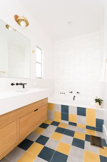 """Myers brightened up the bathroom with an assortment of tiles and a floating wood vanity. Cle Tile's farmhouse brick wall tiles line the tub, backsplash, and shower. The floor is a fresh and random mix of 8"""" square solid cement floor tile in Federal Blue, Ash, and Curry."""