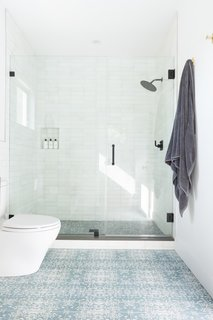 Cle Tile's farmhouse brick wall tiles line theshower. The Omaha floor tiles (from Cle Tile's collaboration with fabric line Eskayel) give the floor of the bathroom instant character.