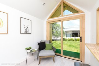 The living space overlooks a three-foot-wide covered patio with artificial turf.