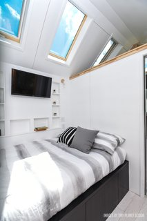 The bedroom features a retracting Apple TV and additional storage space. A 25-gallon fresh water tank lies beneath the bed.