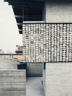 """The texture of the """"flying stone curtain"""" against the traditional rooftops."""