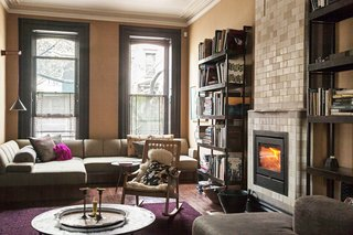 The cozy parlor-floor living room is anchored by a fireplace from the Dutch company Rais.