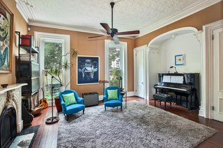 The music room is bright and airy thanks to high ceilings. The renovation preserved the townhouse's original tin ceiling and crown moldings.