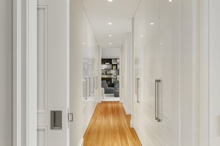A hallway full of storage space leads to a media room.