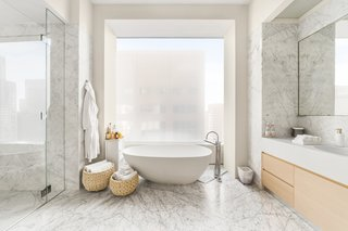 The two light-filled master bathrooms feature marble floors and walls.