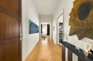 A hallway with herringbone floors leads to the living/dining area.