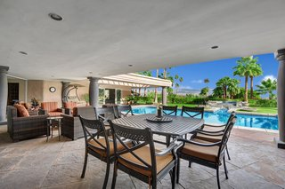 Thecovered outdoor living/dining/entertaining area overlooks the pool.