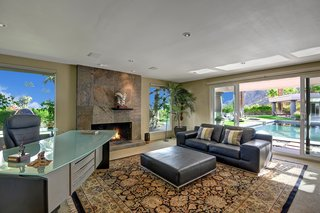 The master suite also includes a sitting area with a fireplace and sliding doors leading out to the pool area.
