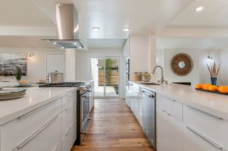 The open kitchen also features a large breakfast island with stone countertops, a gas cooktop, and a double oven.