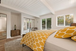 The master suite features double closets,sliding glass doors leading outside, and an ensuite bathroom.