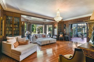 The mansion has multiple spaces for entertaining, including this light-filled living room with bay windows.