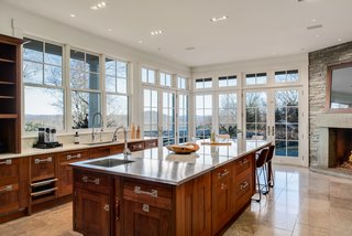 The gourmet kitchen features a large center island with a spacious breakfast bar and top-of-the-line appliances. Extensive glazing keeps the space bright and provides breathtaking views of the surroundings.