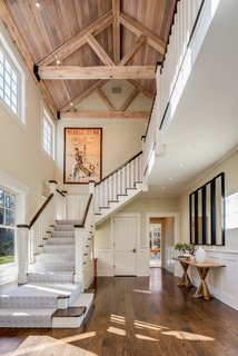 Stairs lead from the entry to the upper level with the bedrooms. The wood-paneled, vaulted ceiling adds warmth to the double-height space.